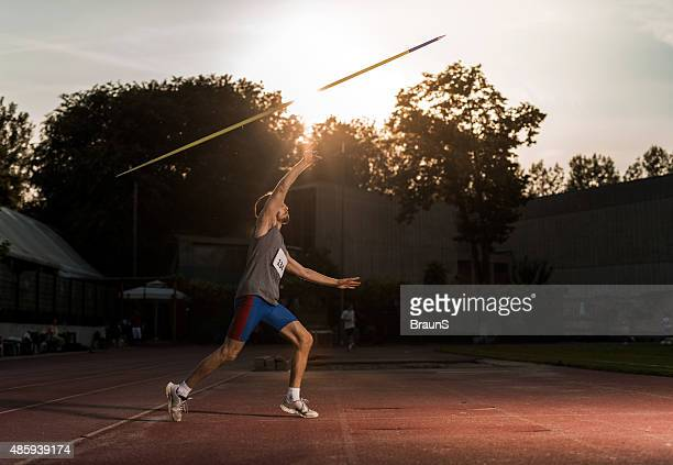 athlete throwing a javelin on a stadium at sunset. - javelin stock pictures, royalty-free photos & images