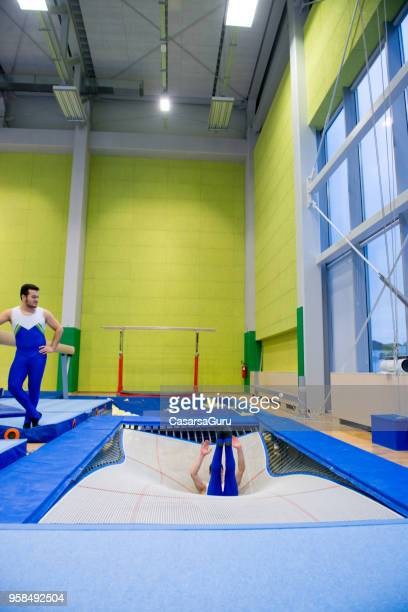 athlete touching down on trampoline - landing touching down stock pictures, royalty-free photos & images