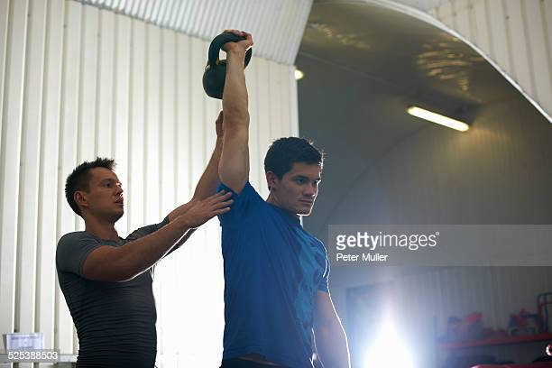 athlete trainer coaching man with kettlebell in gym