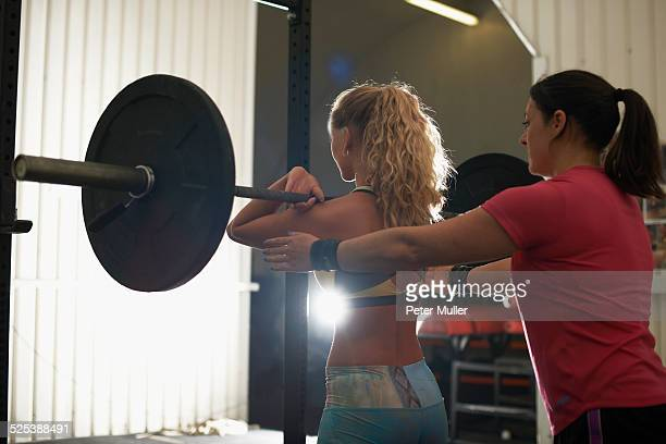 athlete trainer coaching woman with barbell in gym
