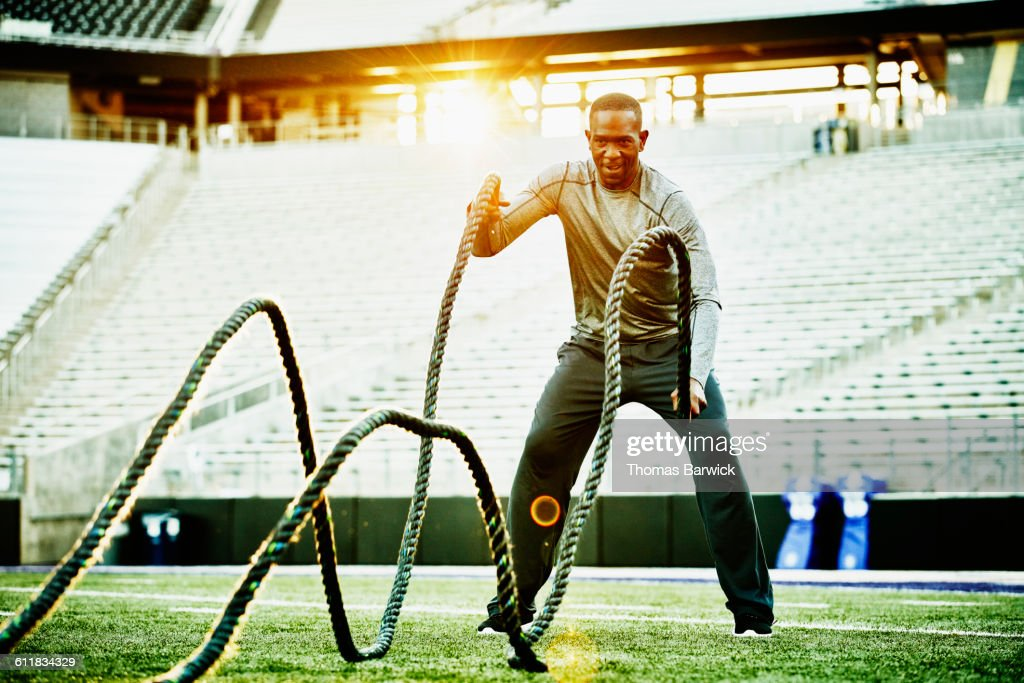 Athlete training with battle rope during workout : Stock Photo
