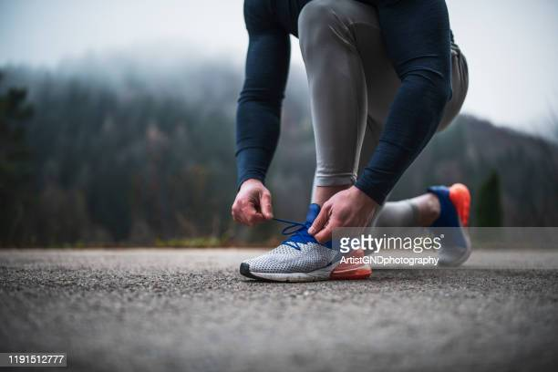 athlete tying shoelace outdoor. - shoelace stock pictures, royalty-free photos & images