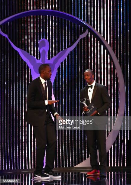 Athlete Usain Bolt of Jamaica accepts his Laureus World Sportsman of the Year Award from Laureus Academy member Michael Johnson on stage during the...