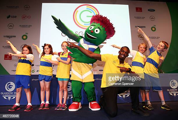 Athlete Usain Bolt of Jamaica poses with Clyde the mascot and children from Giffnock North Amateur Athletics Club during a photocall at the Main...