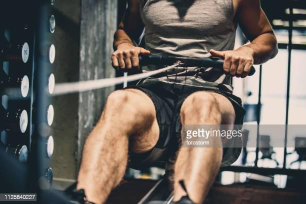 athlete using rowing machine - cavo d'acciaio foto e immagini stock