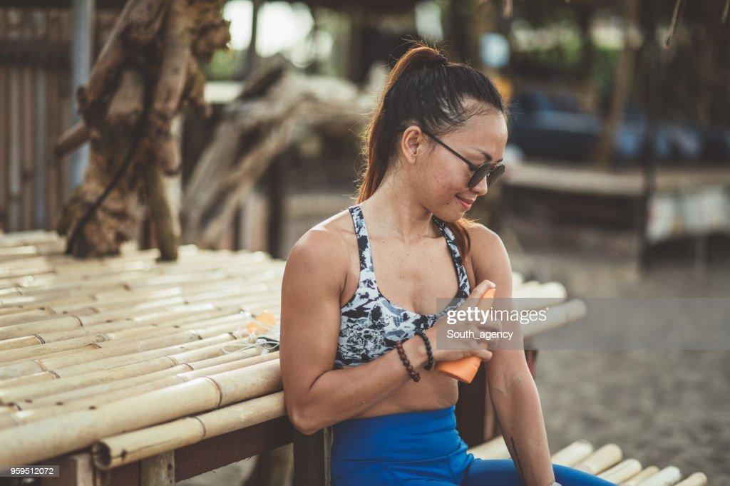 Athlet mit Sonnencreme am Strand : Stock-Foto