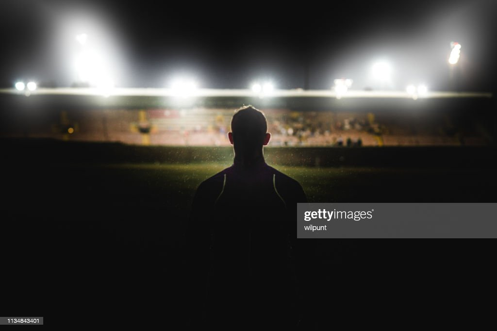 Athlete walking towards stadium silhouette : Stock Photo