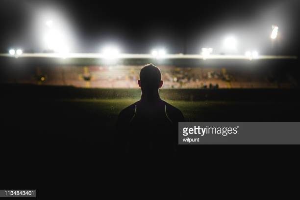 athlete walking towards stadium silhouette - stadio foto e immagini stock