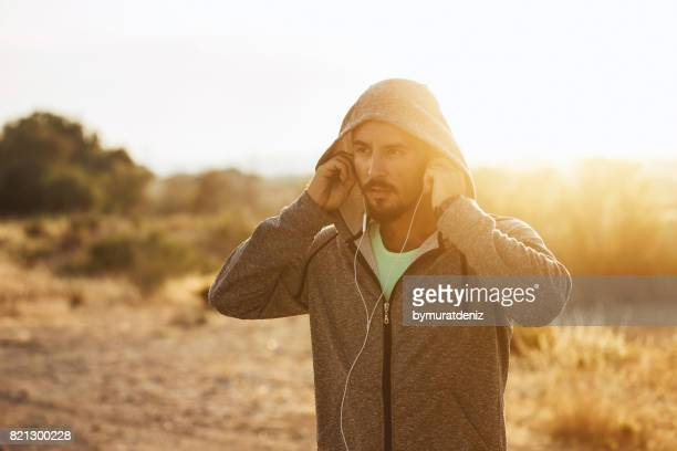 athlete with earphones running - hoodie headphones stock pictures, royalty-free photos & images