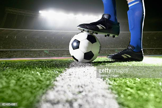 Athlete with foot on soccer ball in stadium