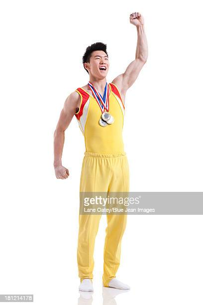 athlete with medals punching the air for winning - medalist stock photos and pictures