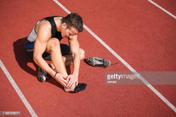 athlete with pain ankle sitting on running track - sprain stock pictures, royalty-free photos & images
