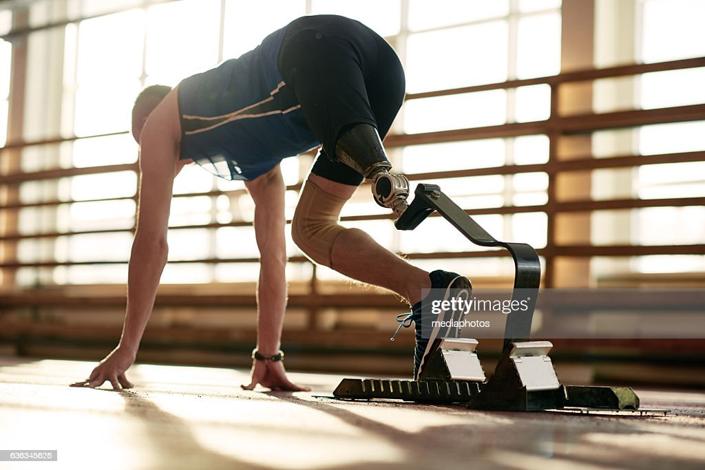 Athlete with prosthetic leg at running track : Stock Photo