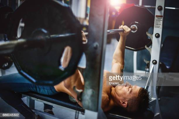 Athlete with six pack abdominal muscles pushing the bar