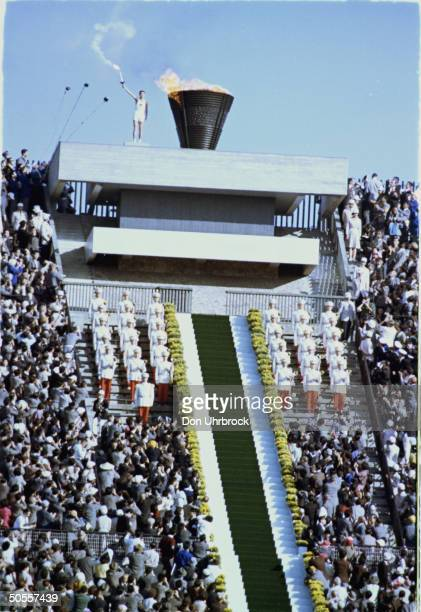 Athlete with torch next to the Eternal Flame during opening ceremonies of the 1964 Summer Olympics in Tokyo Japan