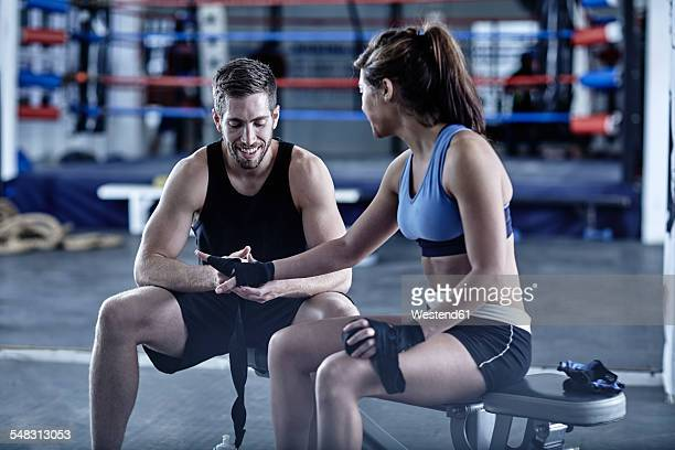Athlete with trainer in gym having a break