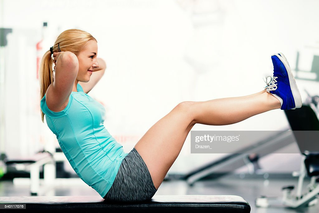 Athlete woman doing sit ups for abdominal muscles in gym : Stock Photo