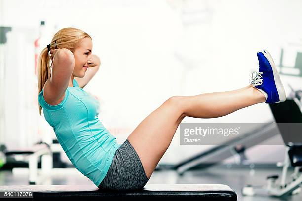 athlete woman doing sit ups for abdominal muscles in gym - circuit training stock photos and pictures