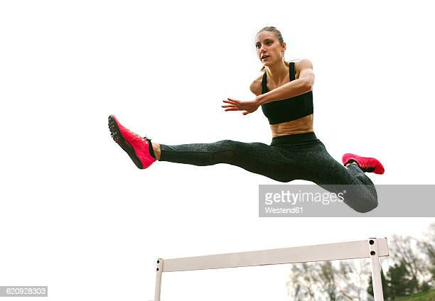 athlete woman jumping in a running track - women's track fotografías e imágenes de stock