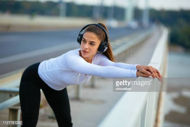 athlete woman leaning forward and stretching while listening to music - forward athlete stock pictures, royalty-free photos & images