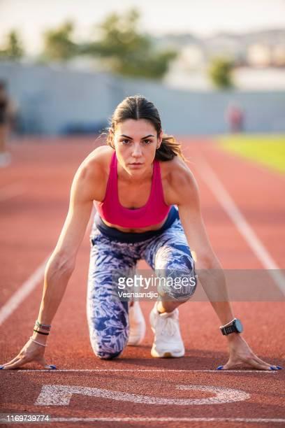 atleta mujer preparándose y corre hurdles para pista y campo - línea de salida fotografías e imágenes de stock