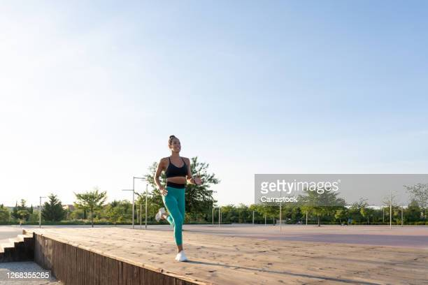 athlete woman running at sunset - kicking stock pictures, royalty-free photos & images