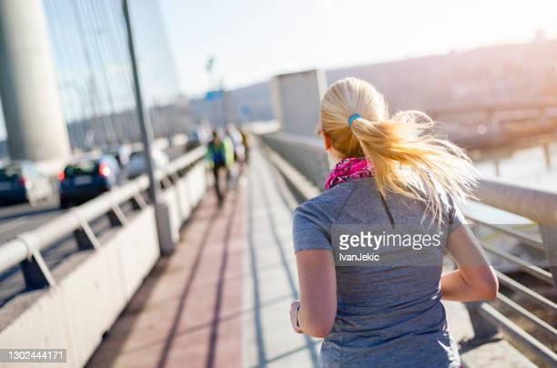 市内を走るアスリート女性 - ゲートル ストックフォトと画像