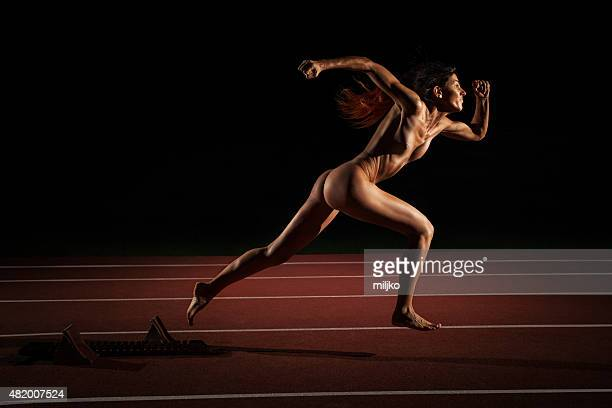 athlete woman running naked on athletic racetrack - atletiek stockfoto's en -beelden