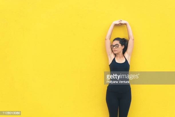 Athlete woman training on the yellow background