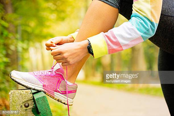 Athlete Woman tying her sneaker