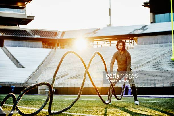 Athlete working out with battle rope in stadium