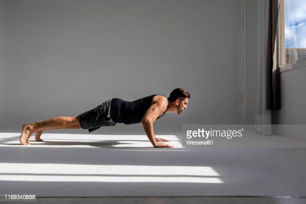 athlete worming up in sunlit studio - push ups stock pictures, royalty-free photos & images