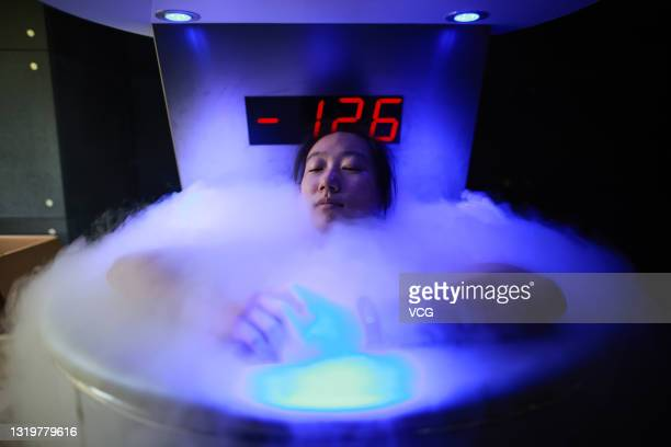Athlete Zhao Dan of Chinese Skeleton Team sits in a liquid nitrogen tank during a training session for the Beijing 2022 Winter Olympic Games at...