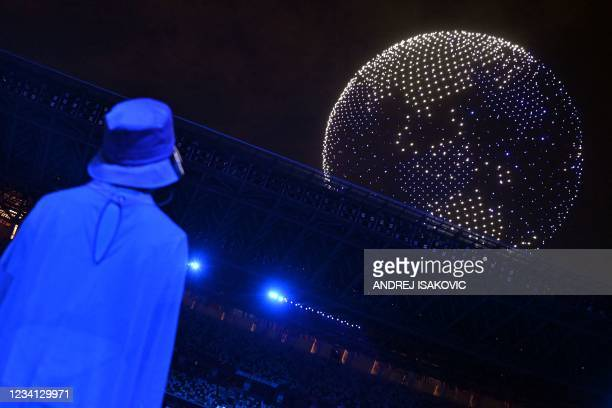 Athletes and volunteers watch a drones flying to form a globe in the sky over the Olympic Stadium during the opening ceremony of the Tokyo 2020...