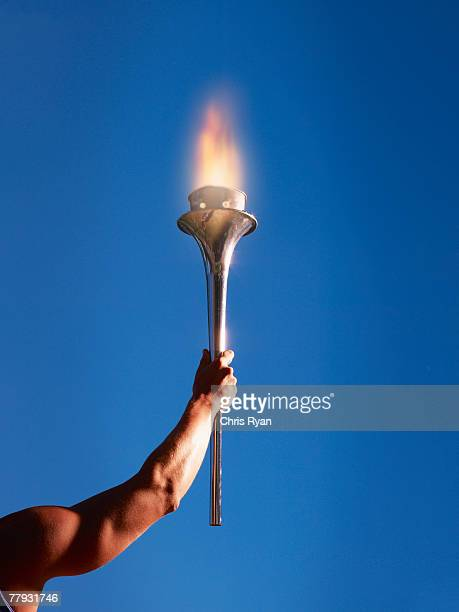 athlete's arm holding up a torch - flame stock pictures, royalty-free photos & images