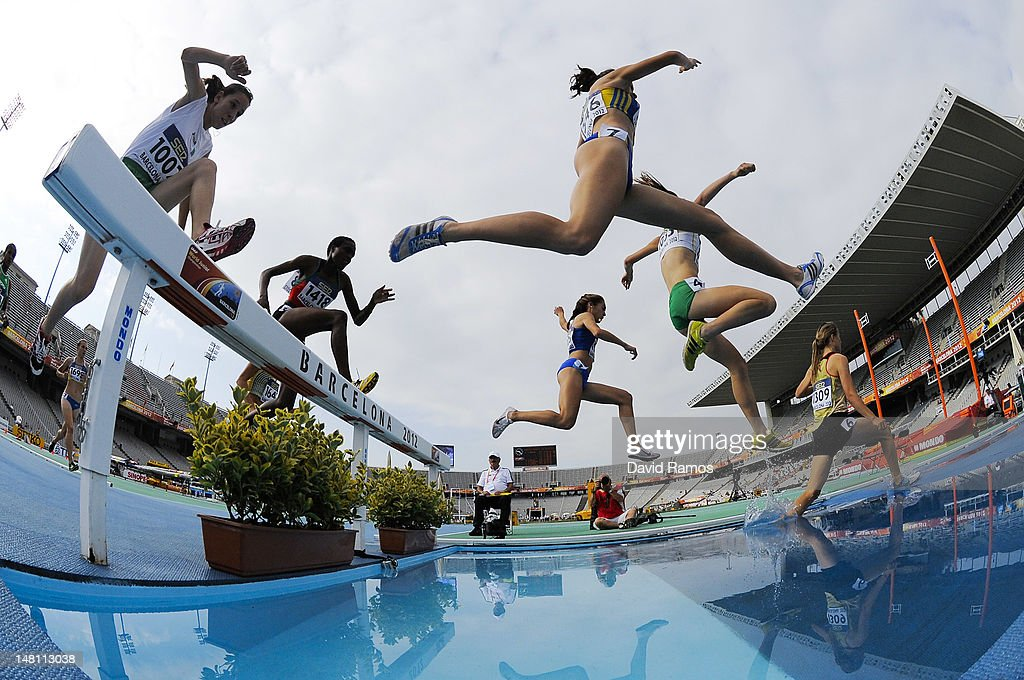 Athletes attempt to clear the water jump during the Women's 3000 metre Steepechase qualification heat on the day one of the 14th IAAF World Junior Championships at Estadi Olimpic Lluis Companys on July 10, 2012 in Barcelona, Spain.