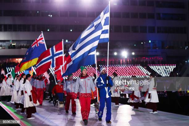Athletes carry their national flags to take part in the closing ceremony of the 2018 Winter Paralympics during the closing ceremony of the...