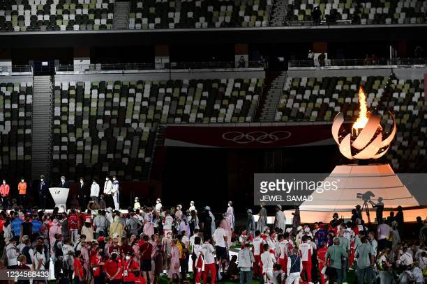 Athletes celebrate next to Olympic Cauldron and the Olympic flame during the closing ceremony of the Tokyo 2020 Olympic Games, at the Olympic...