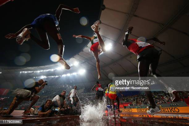 Athletes clear the water jump in the Men's 3000 metres Steeplechase final during day eight of 17th IAAF World Athletics Championships Doha 2019 at...