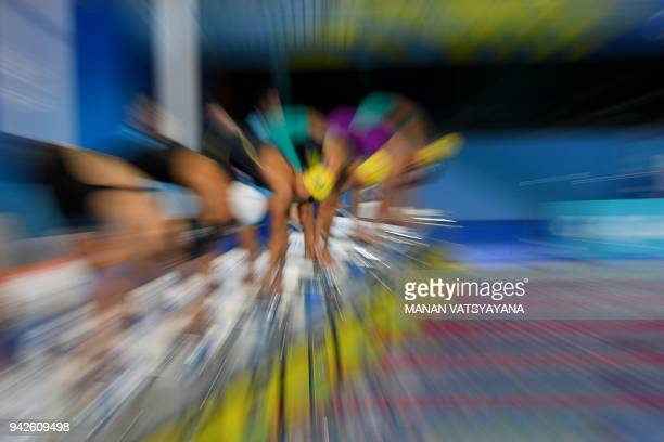 Athletes compete during the swimming women's 100m butterfly final during the 2018 Gold Coast Commonwealth Games at the Optus Aquatic Centre in the...