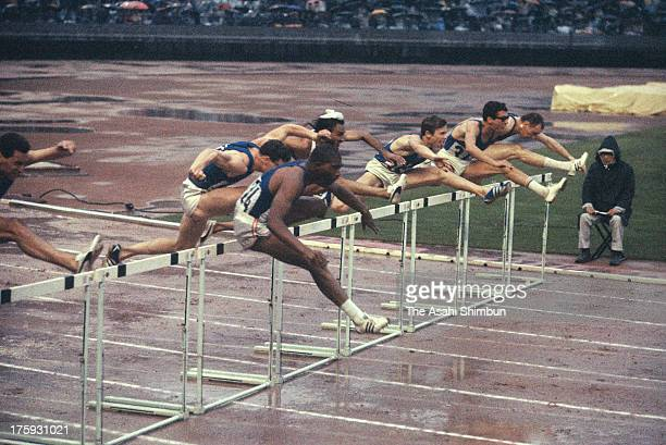Athletes compete in the Men's 110m Hurdles Final during the Tokyo Olympic at the National Stadium on October 18 1964 in Tokyo Japan