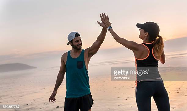Athletes couple hitting five on the beach at sunset