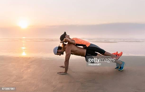 Athletes couple training on the beach at sunset, pushups