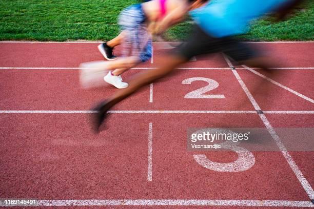 atleten die de finish lijn oversteken - teamevenement stockfoto's en -beelden