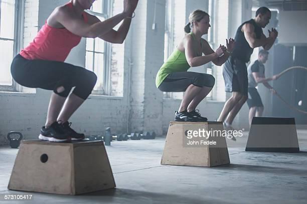 Athletes crouching on platforms in gym