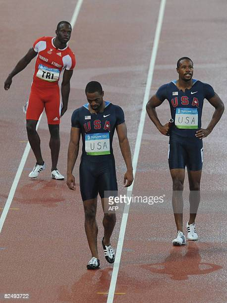 US athletes Darvis Patton and Tyson Gay look dejected next to Trinidad and Tobago's Aaron Armstrong after being disqualified during the men's 4x100m...