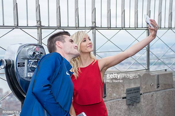 Athletes David Boudia and Nastia Liukin take a selfie as Team USA Athletes light the Empire State Building red white and blue to celebrate the 100...