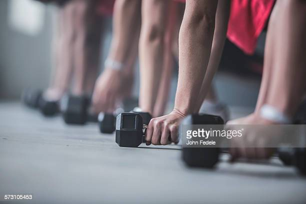 Athletes doing push-ups and lifting weights on floor