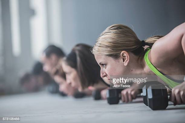 athletes doing push-ups and lifting weights on floor - concentration stock pictures, royalty-free photos & images