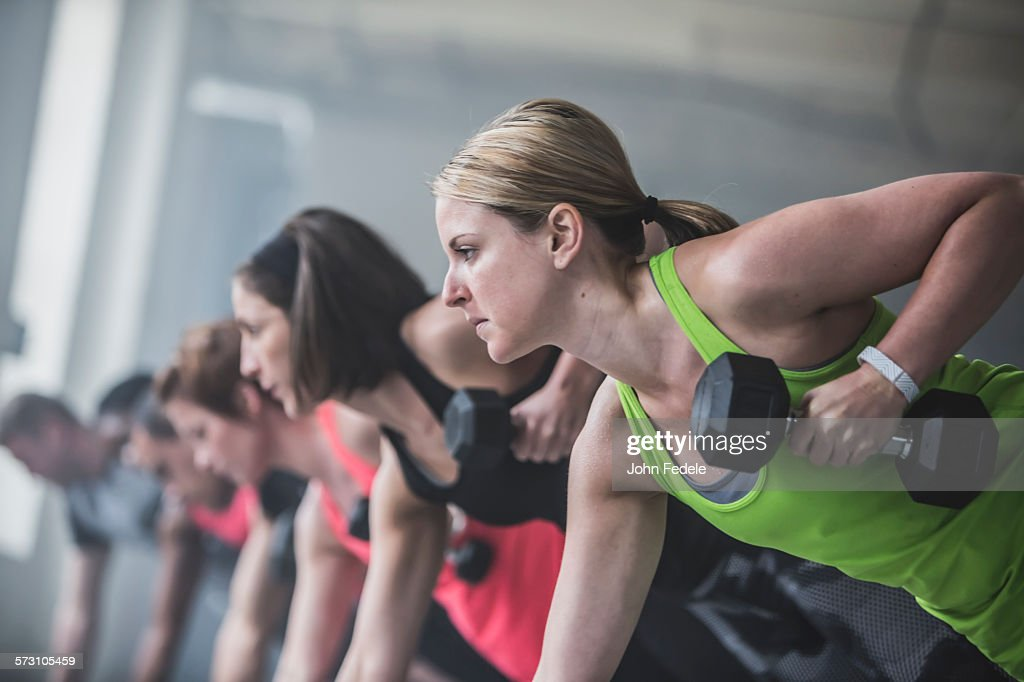 Athletes doing push-ups and lifting weights : Stock Photo